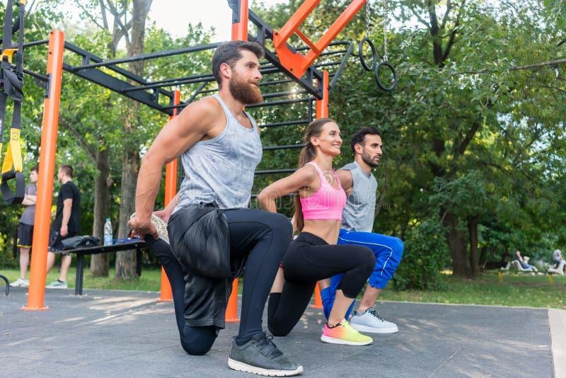 Drei bestimmten die Freunde, die Übungen für Beine wie ausdehnend tun lizenzfreie stockfotos
