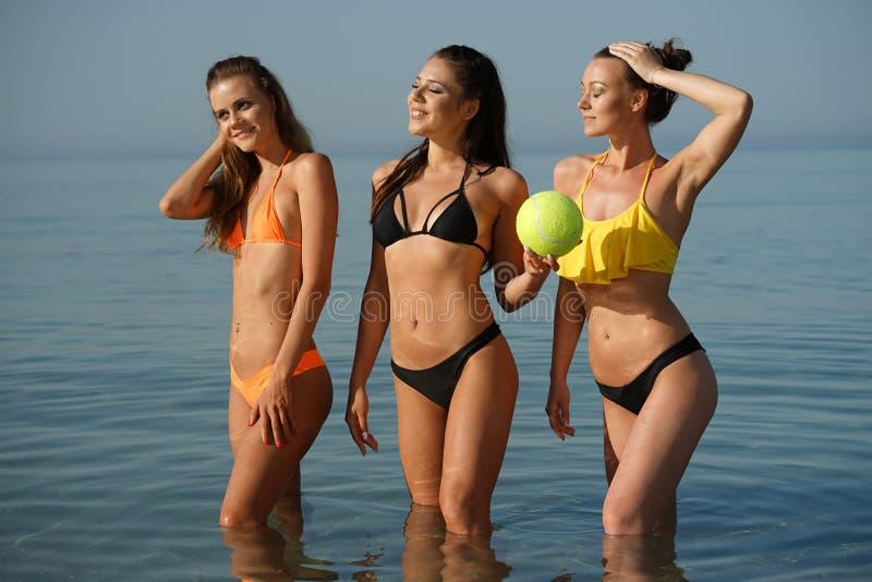 Drei Bikinifrauen im Meer mit Ball lizenzfreies stockfoto