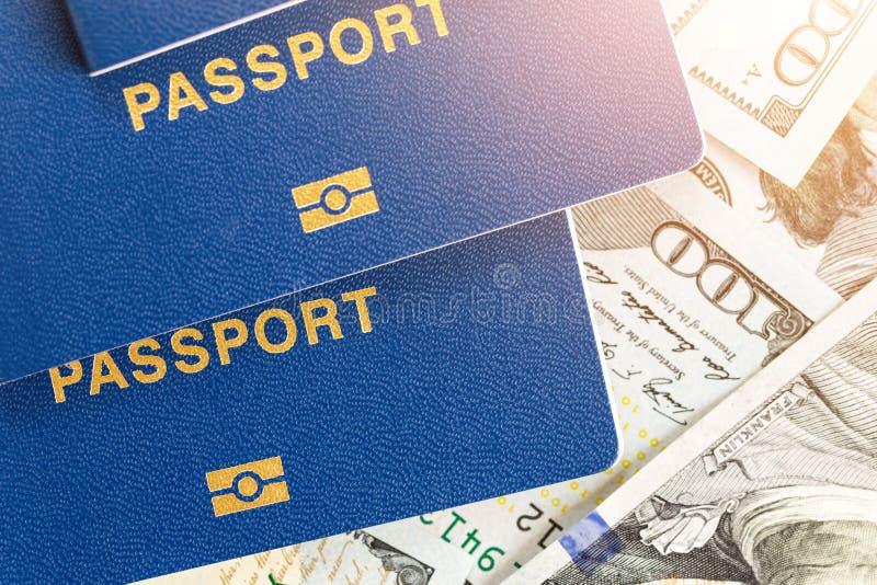 Drei biometrical internationale Pässe über Geldhintergrund Blaue Reisedokumente, die auf US hundert Dollarbanknoten liegen f stockbilder