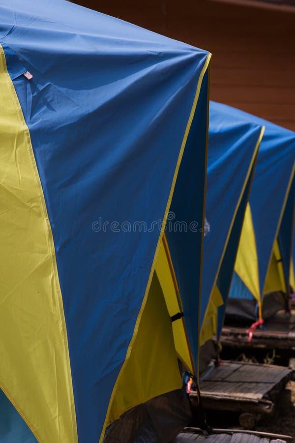 Drei blau und gelbe Zelte in Folge lizenzfreie stockbilder