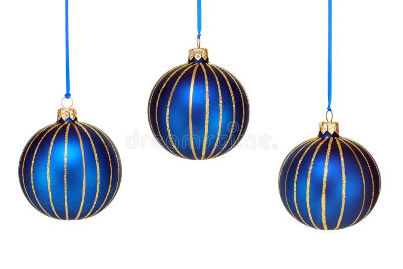 Drei blau und Goldweihnachtsverzierungen auf Weiß lizenzfreie stockfotos