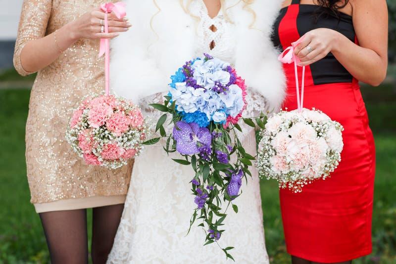 Drei Brautjungfern, die Blumensträuße halten stockfoto