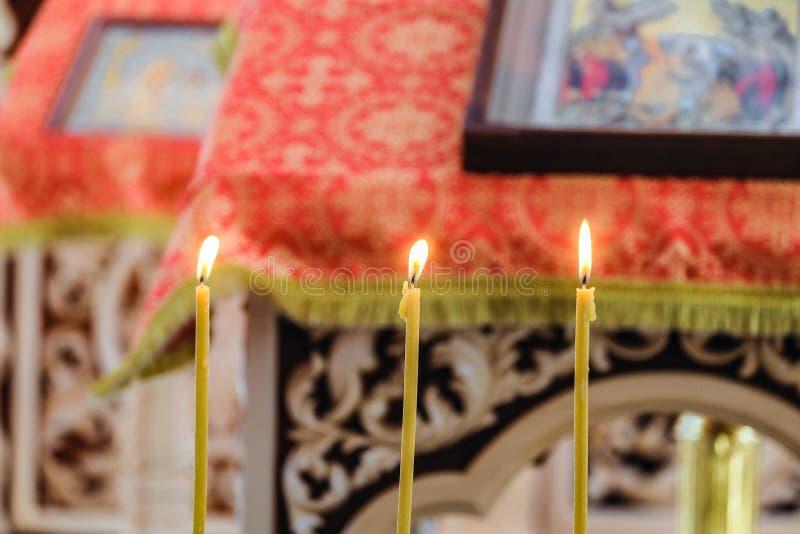 Drei brennende Kerzen auf einem unscharfen Hintergrund der Kanzel mit einer Ikone für Liturgie, Gebete und Predigten lizenzfreies stockbild