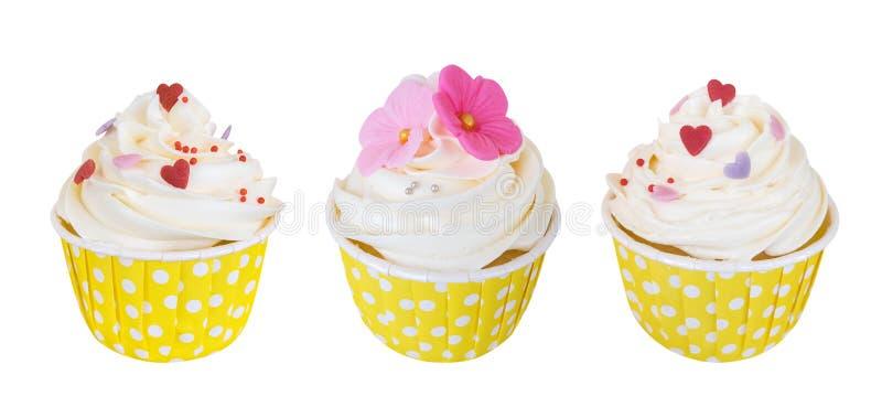 Drei Buttersahnekleine kuchen mit süßen Blumen und Herzen in der Tupfenpapierschale lokalisiert auf weißem Hintergrund, Weg lizenzfreie stockfotografie