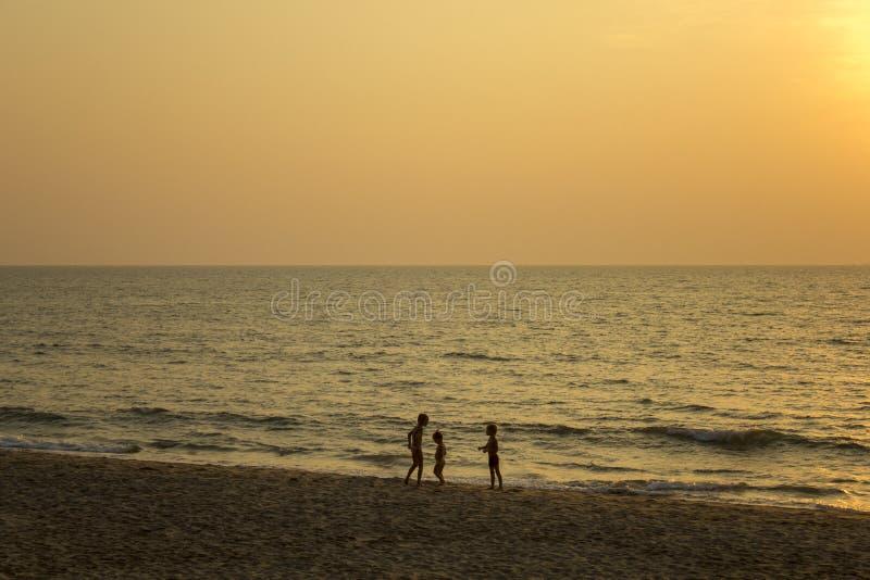 drei dunkle Schattenbilder von Kindern auf dem mit gelbem Sand des Strandes gegen das Meer und den Abend stockfoto