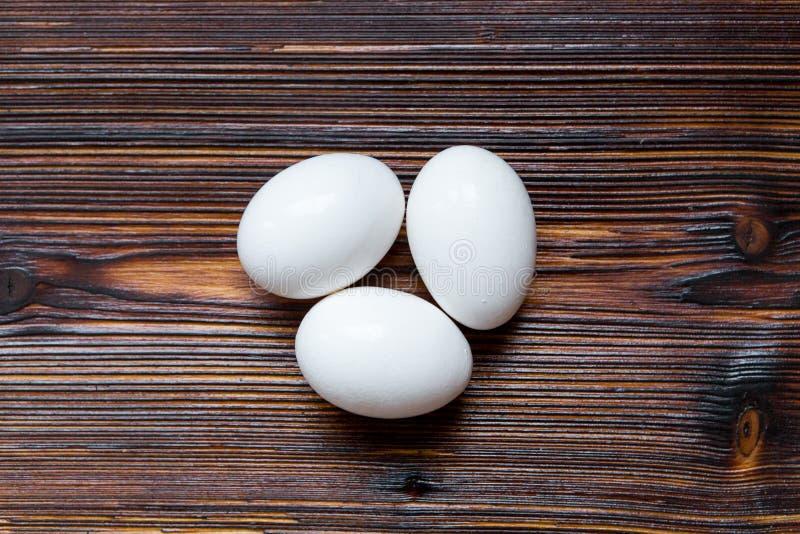 Drei Eier auf einem hölzernen Hintergrund lizenzfreie stockfotografie