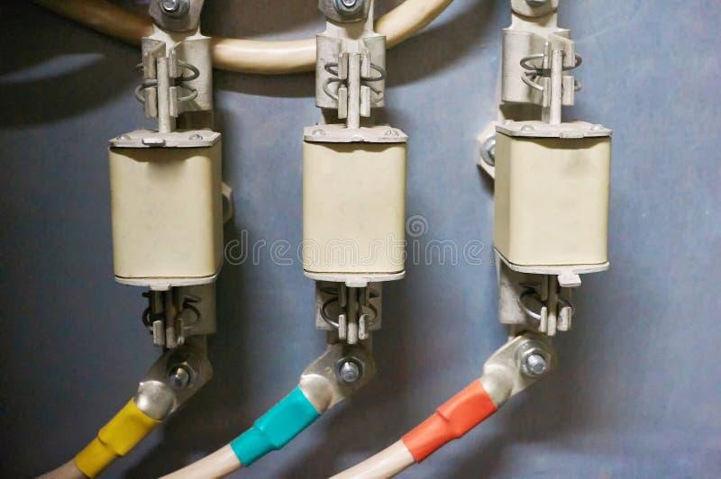 Drei elektrische Hochspannungssicherungen angeschlossen an die farbigen Drähte Industrieller Hintergrund stockbild