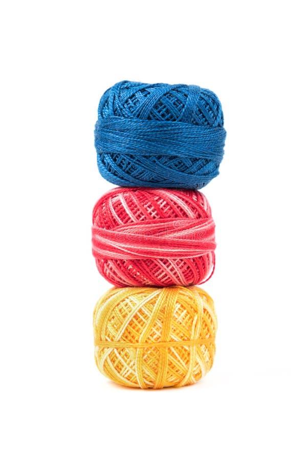 Drei färbten Nähgarne in Folge auf einem weißen vertikalen Hintergrund Blaue, rote und gelbe Threads lizenzfreies stockfoto