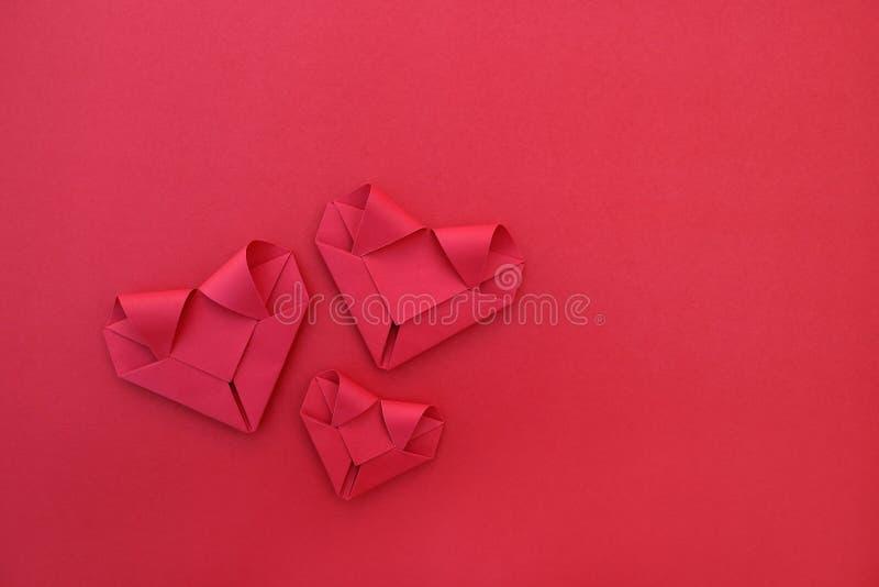 drei faltende rote Papierherzen auf Rot für Muster und Hintergrund stockbild