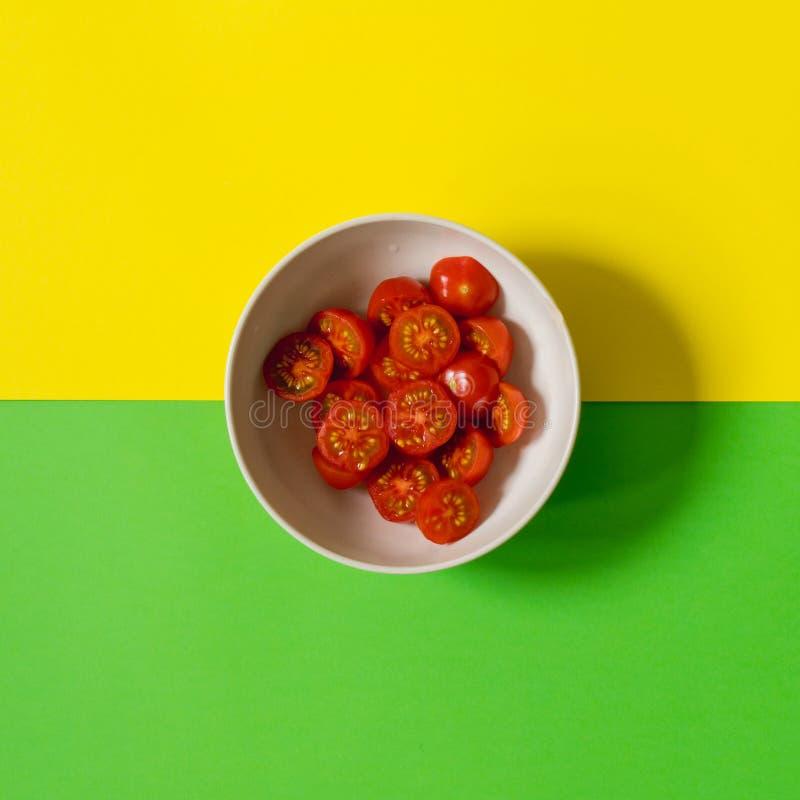 Drei Farben sind rot grün, gelb und Kirschtomaten in einer Platte auf einem Hintergrund des gelben und grünen Hintergrundes lizenzfreie stockbilder