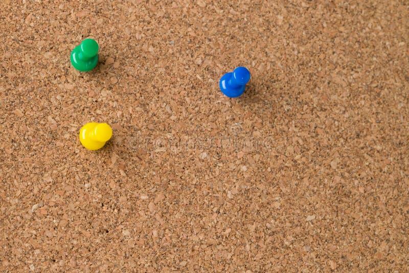 Drei farbige Daumen-Reißnägel auf Cork Board stockbilder