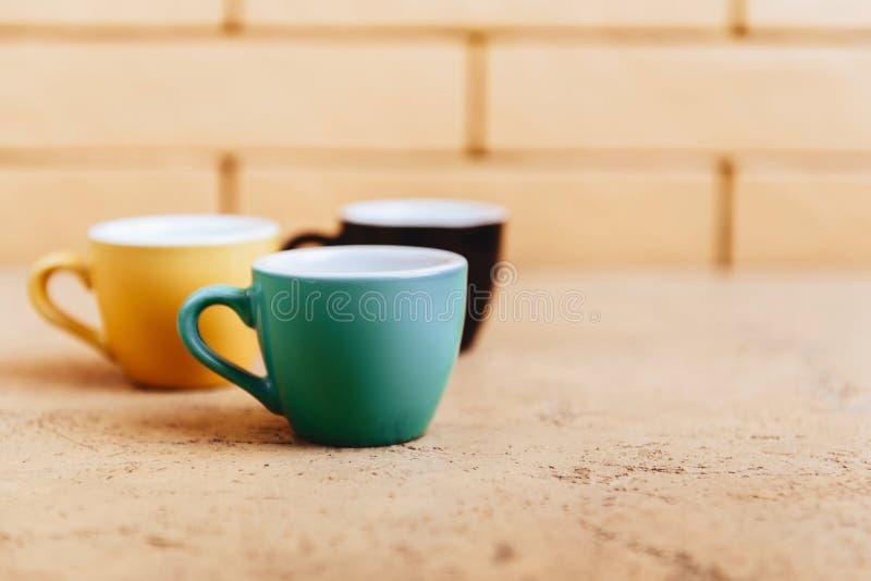 Drei Farbkaffeetassen auf hellem Hintergrund stockbild