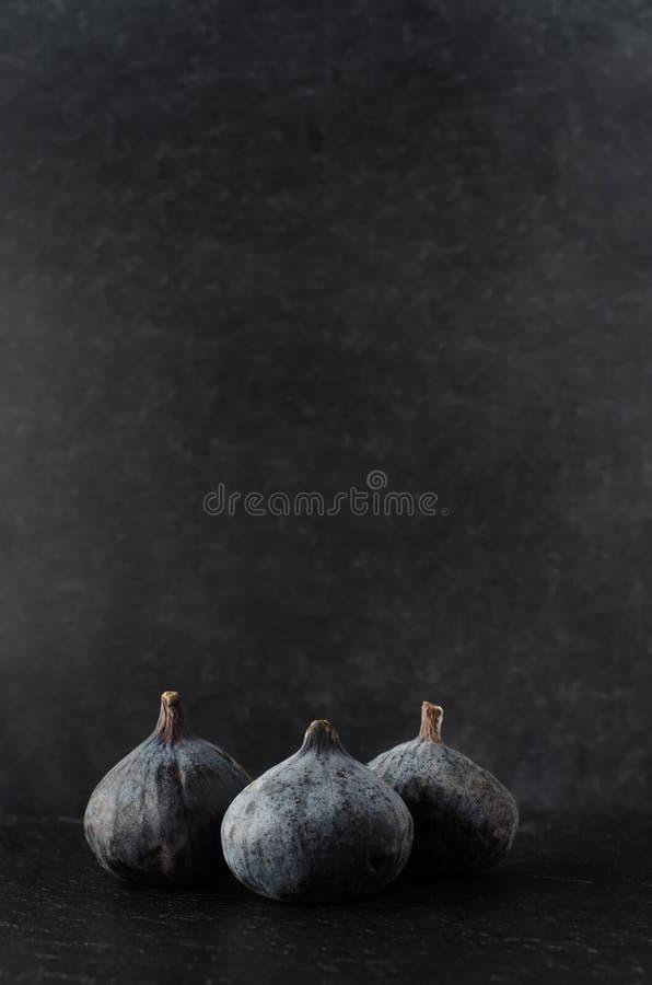 Drei Feigen gruppiert auf Schwarzem lizenzfreie stockfotos