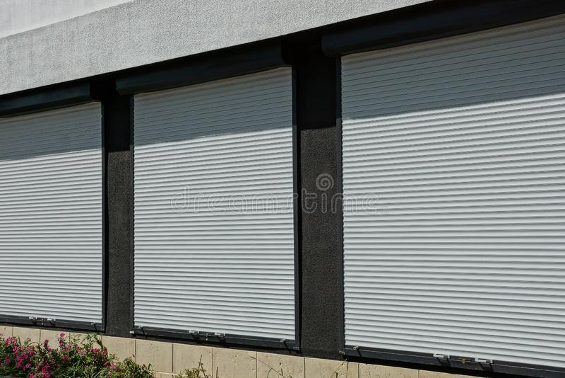 Drei Fenster bedeckt mit weißen Plastikfensterläden auf der Wand des Hauses stockfoto