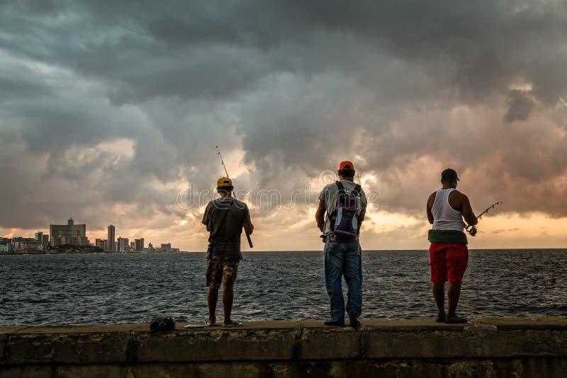 Drei Fischer bei dem Sonnenuntergang beleuchtet Stellung auf dem Malecon-str stockfoto