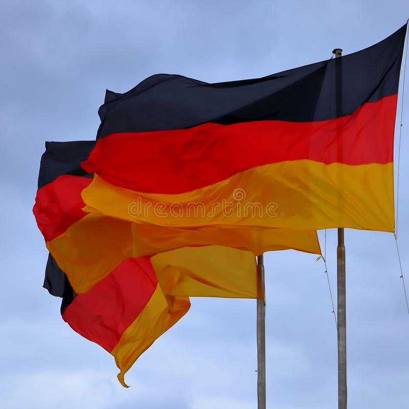 Drei Flaggen Deutschland, deutsche Flagge, die im Wind durchbrennt lizenzfreie stockfotos