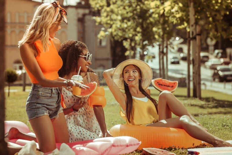 Drei Frauen appellieren, die draußen ein Lachen während eines Picknicks teilen stockfotos