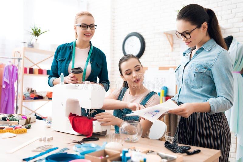 Drei Frauen an der Kleiderfabrik Eins von ihnen Plan zeigend stockbild