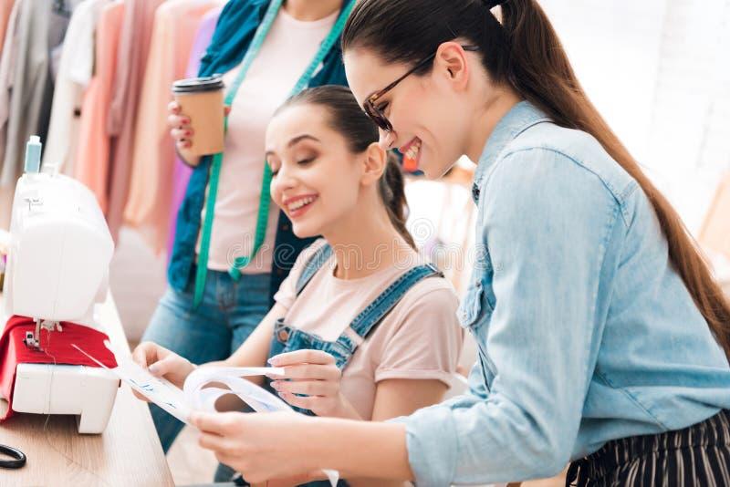 Drei Frauen an der Kleiderfabrik Eins von ihnen Plan zeigend lizenzfreies stockfoto
