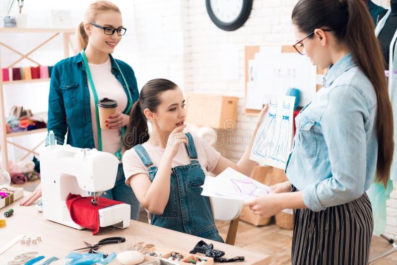 Drei Frauen an der Kleiderfabrik Sie betrachten Pläne stockfoto