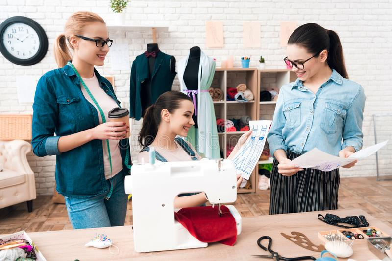 Drei Frauen an der Kleiderfabrik Sie betrachten Pläne lizenzfreies stockfoto