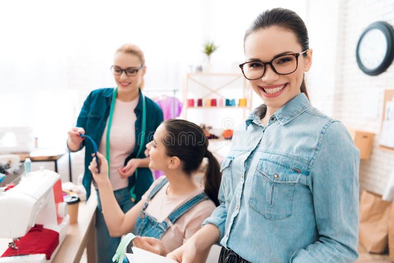 Drei Frauen an der Kleiderfabrik Sie wählen Reißverschlüsse für das Kleid stockbild