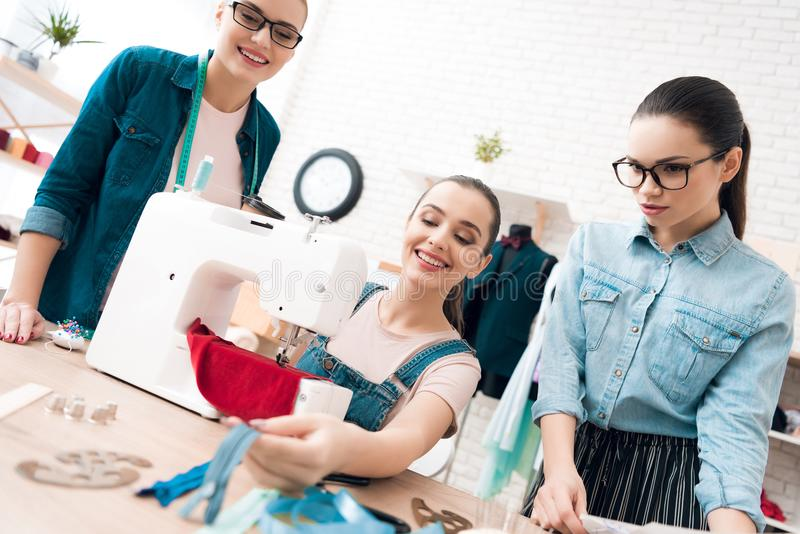 Drei Frauen an der Kleiderfabrik Sie wählen Reißverschlüsse für das Kleid stockfotografie