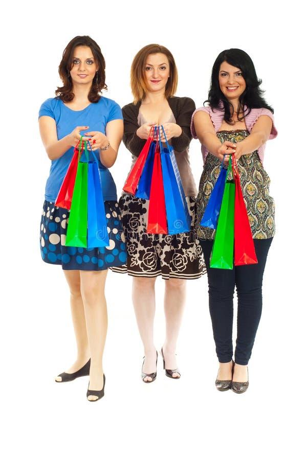 Drei Frauen, die Einkaufenbeutel geben stockfotografie