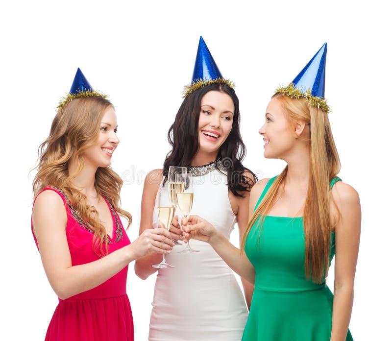 Drei Frauen, die Hüte mit Champagnergläsern tragen stockfoto