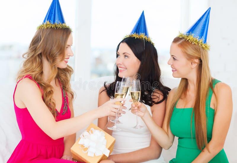 Drei Frauen, die Hüte mit Champagnergläsern tragen stockbild
