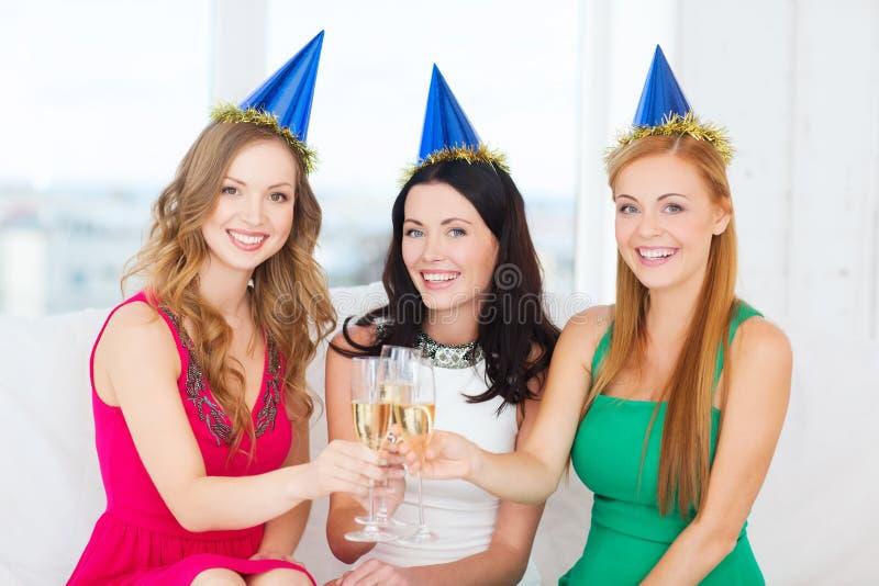 Drei Frauen, die Hüte mit Champagnergläsern tragen lizenzfreie stockfotos