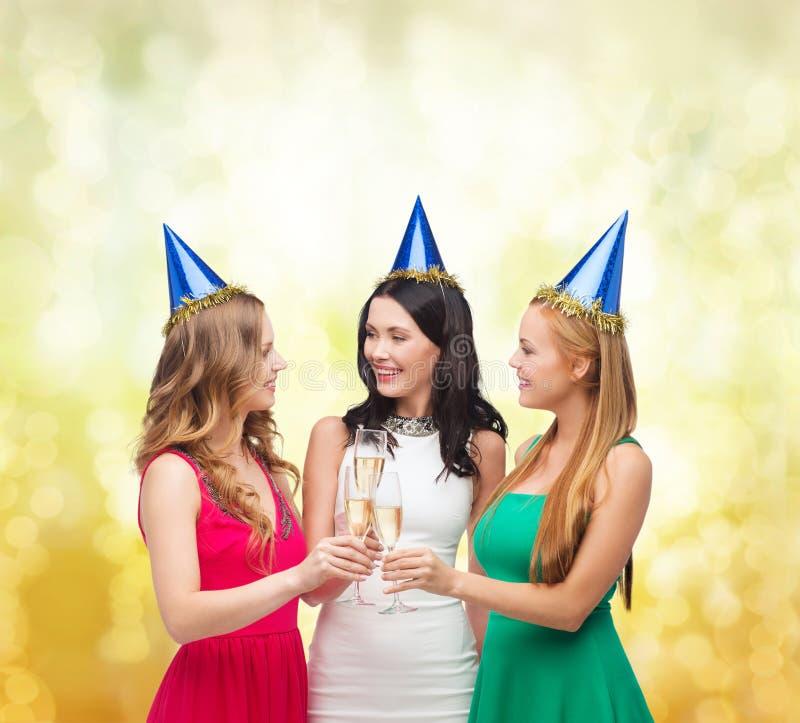 Drei Frauen, die Hüte mit Champagnergläsern tragen stockfotografie