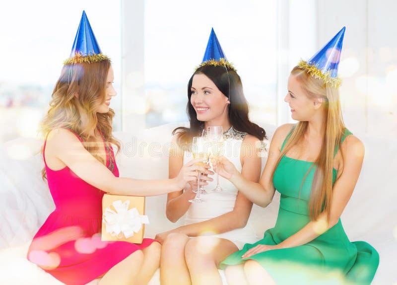 Drei Frauen, die Hüte mit Champagnergläsern tragen lizenzfreies stockbild