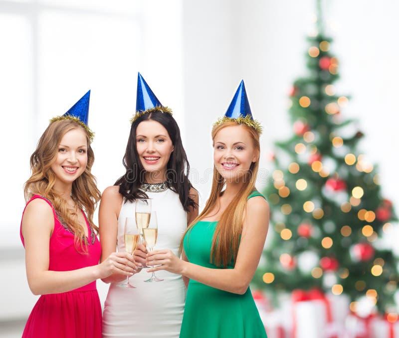 Drei Frauen, die Hüte mit Champagnergläsern tragen stockfotos
