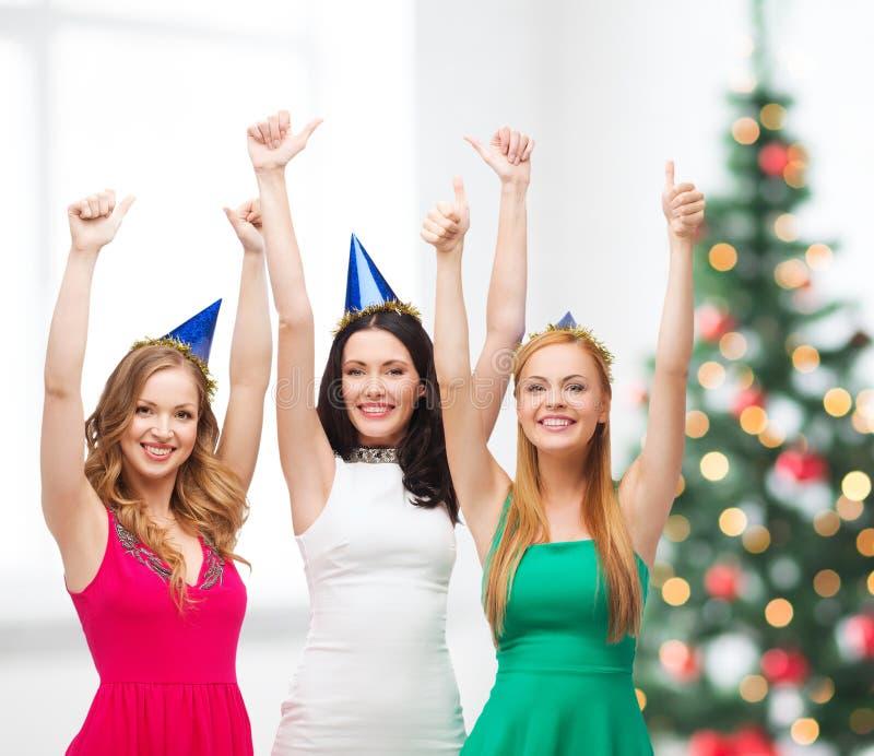 Drei Frauen, die Hüte tragen und sich Daumen zeigen stockbilder