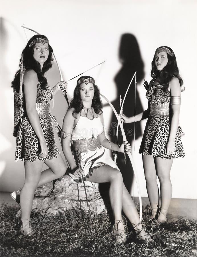 Drei Frauen gekleidet in Amazonas-Kostümen stockbild