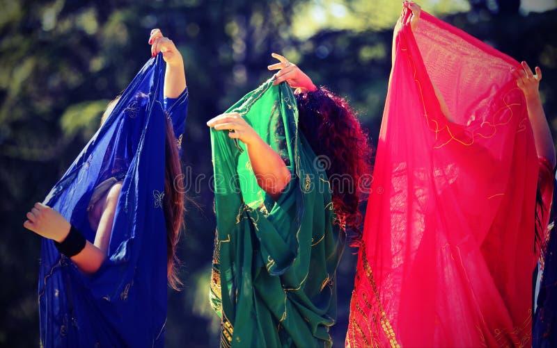 Drei Frauen während eines sinnlichen Tanzes mit langer bunter Kleidung stockfotos