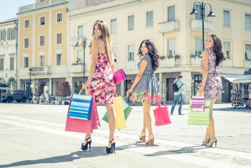 Drei Freunde, die das Einkaufen machen stockfotografie