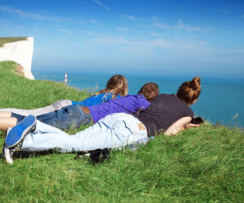 Drei Freunde, die einen Leuchtturm betrachten lizenzfreie stockfotografie