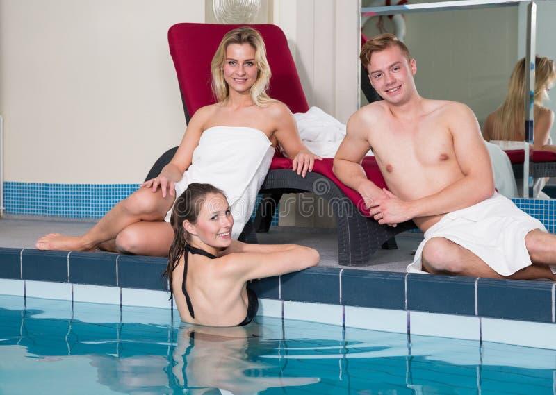 Drei Freunde, die einen Tag am HotelSwimmingpool genießen stockfotos