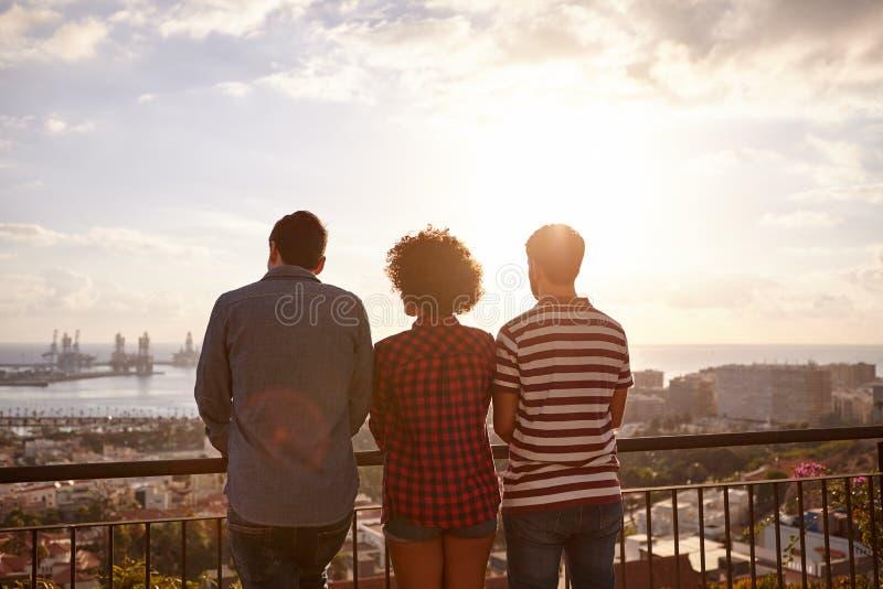Drei Freunde, die heraus über Stadt schauen stockbild