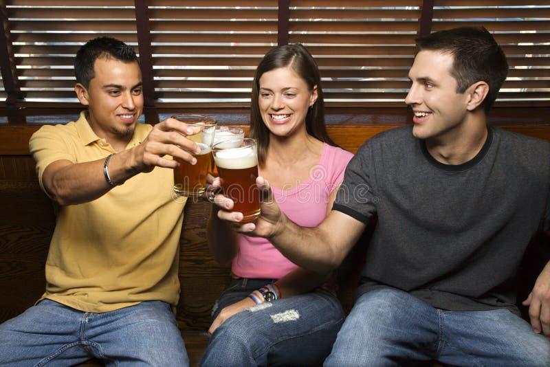 Drei Freunde, die mit Bieren rösten stockfoto