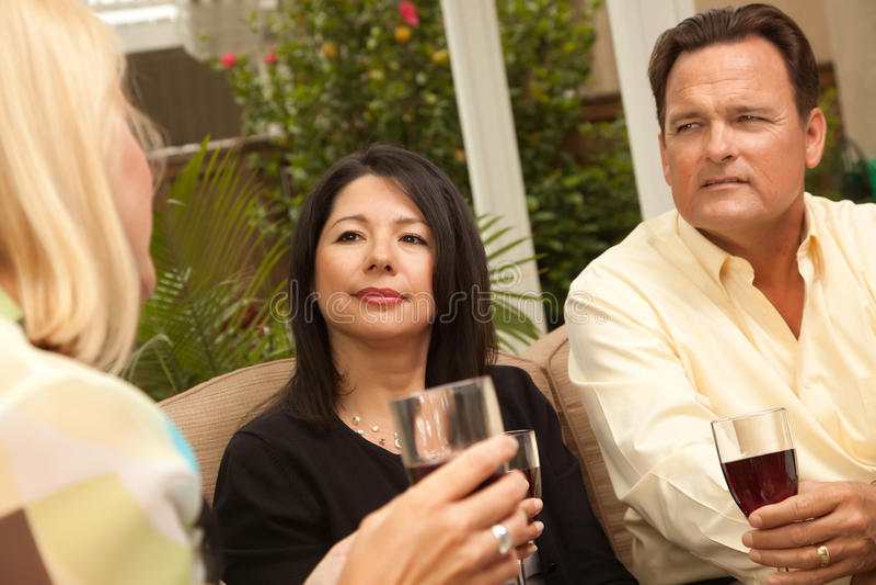 Drei Freunde, die Wein auf dem Patio genießen lizenzfreie stockfotos