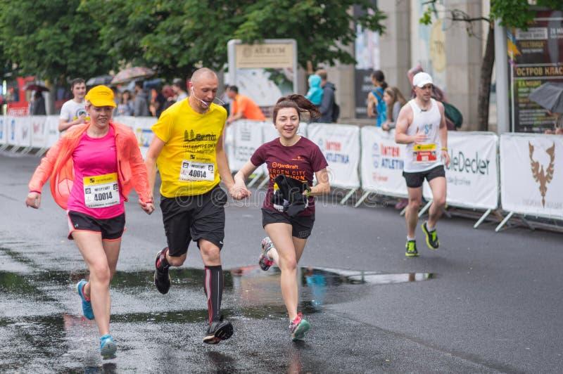 Drei Freunde, die zusammen auf der zentralen Straße von Dnipro-Stadt während des Halbmarathon ` Interipe Dnipro ` Rennens laufen lizenzfreie stockfotos