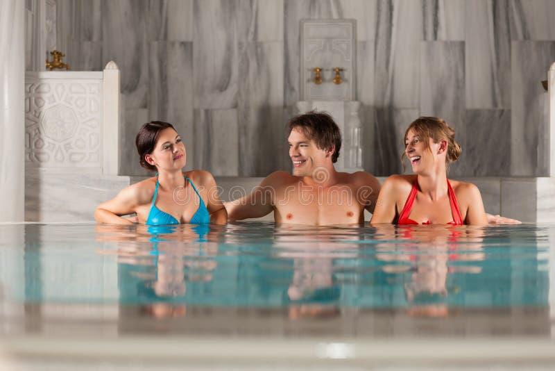 Drei Freunde im Swimmingpool oder im thermischen Bad lizenzfreie stockfotografie