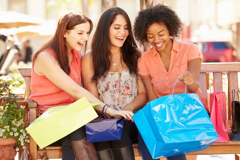 Drei Freundinnen mit den Einkaufstaschen, die im Mall sitzen stockfotos