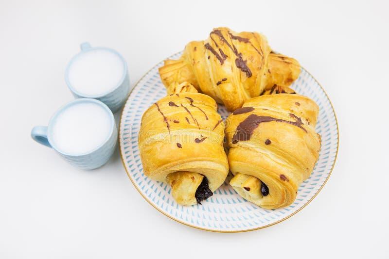 Drei frisch gebackene Hörnchen auf einer weißen keramischen Platte, zwei Tasse Kaffees stockfotografie