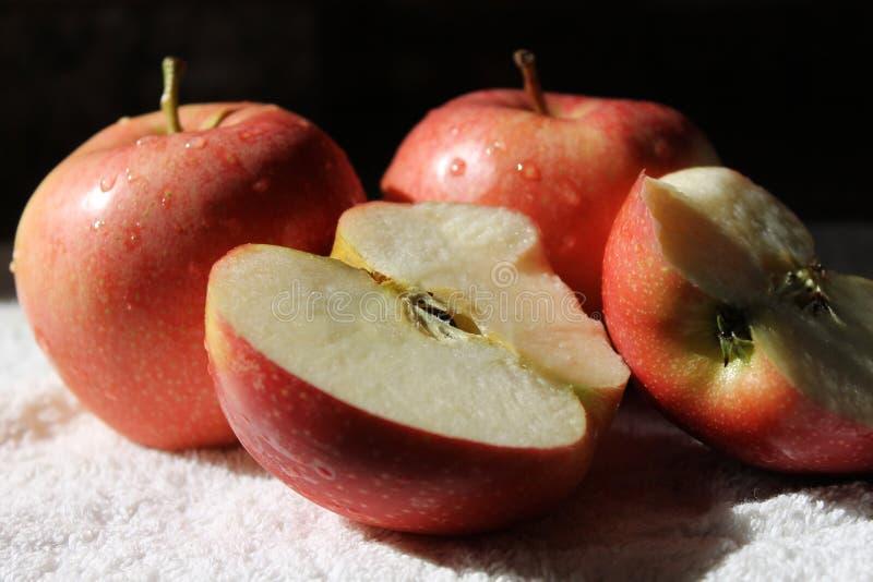Drei frische rote Äpfel und eins von ihnen um eine Hälfte sich aufspalten lizenzfreies stockbild