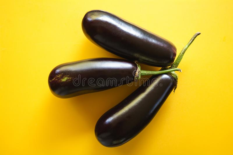 Drei frische schwarze organische Auberginen auf einem gelben Hintergrund, Draufsicht stockbilder