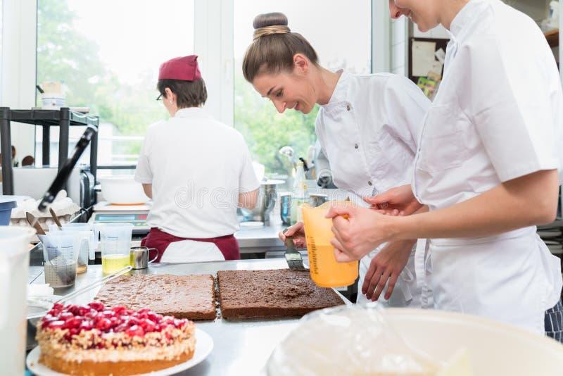 Drei Gebäckbäcker in den Süßigkeiten, die Fruchttorten zubereiten stockfotos